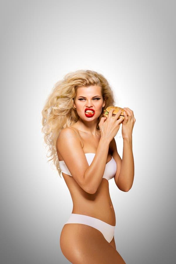 Äta hamburgare royaltyfria bilder