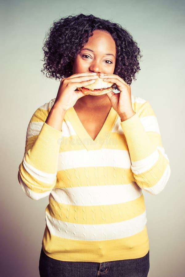 äta hamburgarekvinnan royaltyfria bilder
