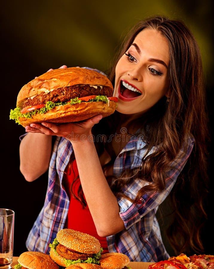 äta hamburgarekvinnan Flickatugga av den mycket stora hamburgaren royaltyfria bilder