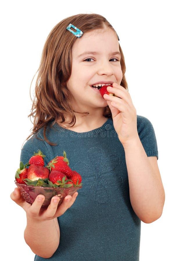 äta lilla jordgubbar för flicka arkivbild