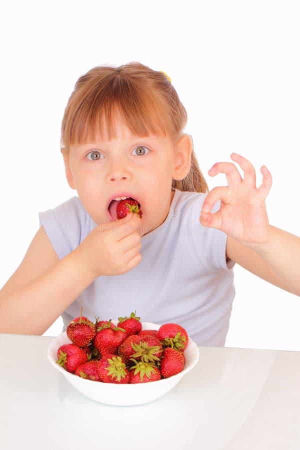 äta lilla nätt jordgubbar för flicka arkivbild