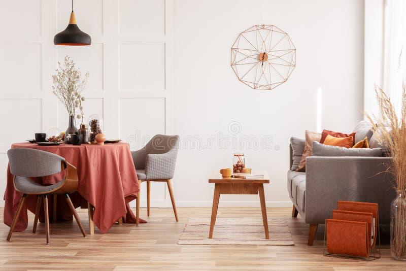 Äta middag för öppet utrymme och bosatt område med den gråa scandinavian soffan och tabellen med stolar arkivbilder