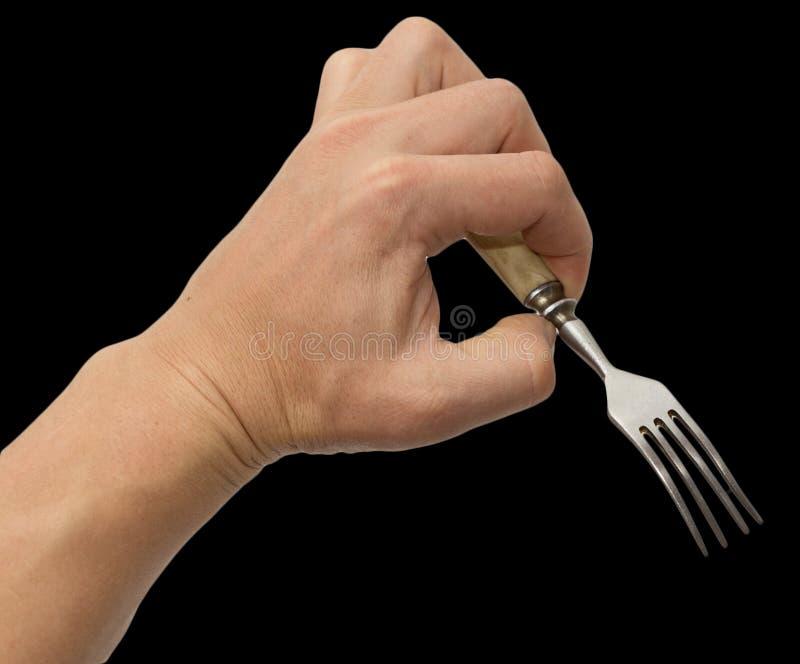 Äta middag gaffeln i hand på en svart bakgrund arkivfoton