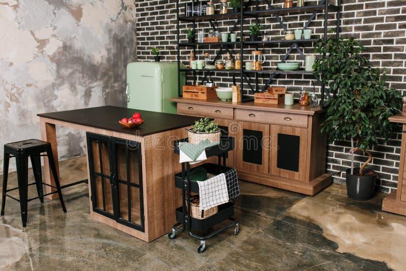 Äta middag område i industriell stil med tabellen, stolar och den retro kylen för mintkaramell Svart bakgrund för tappningtegelst royaltyfri fotografi