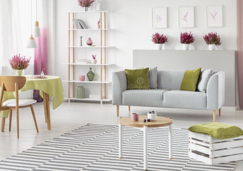 Äta middag tabell med den gröna bordduken i ljus scandinavian vardagsrum med vitt och trämöblemang, grå soffa och randigt arkivbild