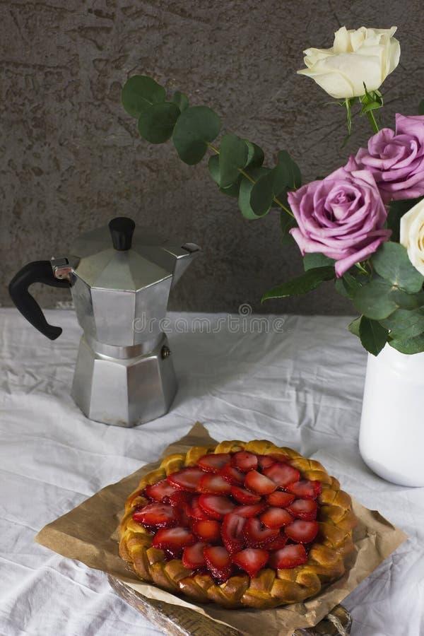 Äta middag tabellen med den blomma-, kaffebryggare- och jordgubbepajen royaltyfria bilder