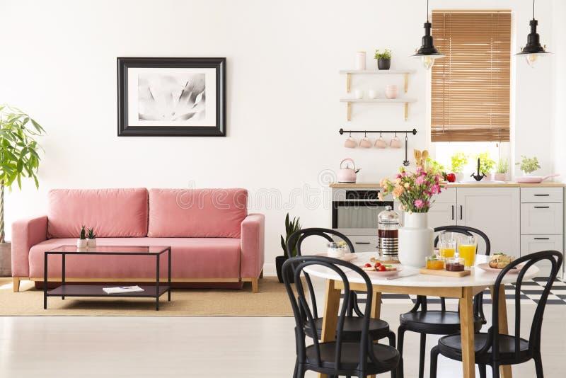 Äta middag tabellen med frukosten och nya blommor som står i ljust arkivfoton
