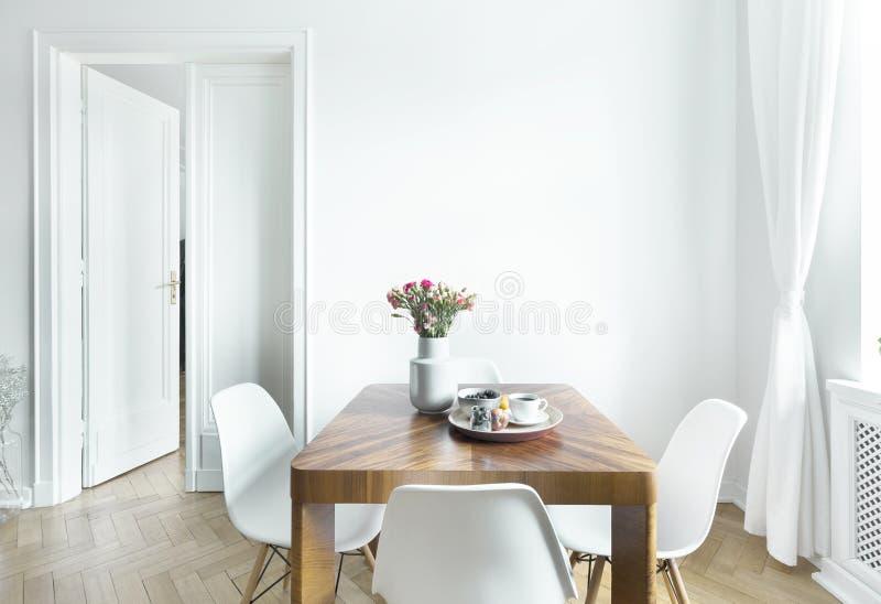 Äta middag tabellen med nya blommor och frukostmagasinet med kaffekoppen och frukter i verkligt foto av inre för vitt rum med den arkivbild