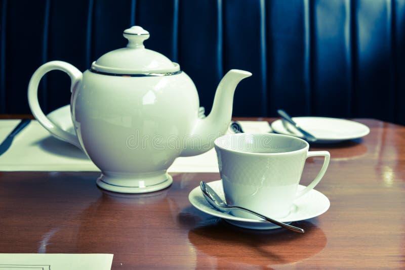 Äta middag tabellen med te och tekannan royaltyfria bilder