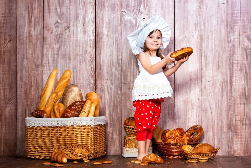 Äta nytt bröd och hemlagade bakelser Liten le flicka i ett kocklock med bageln i hand nära en vide- korg med brödrullar fotografering för bildbyråer