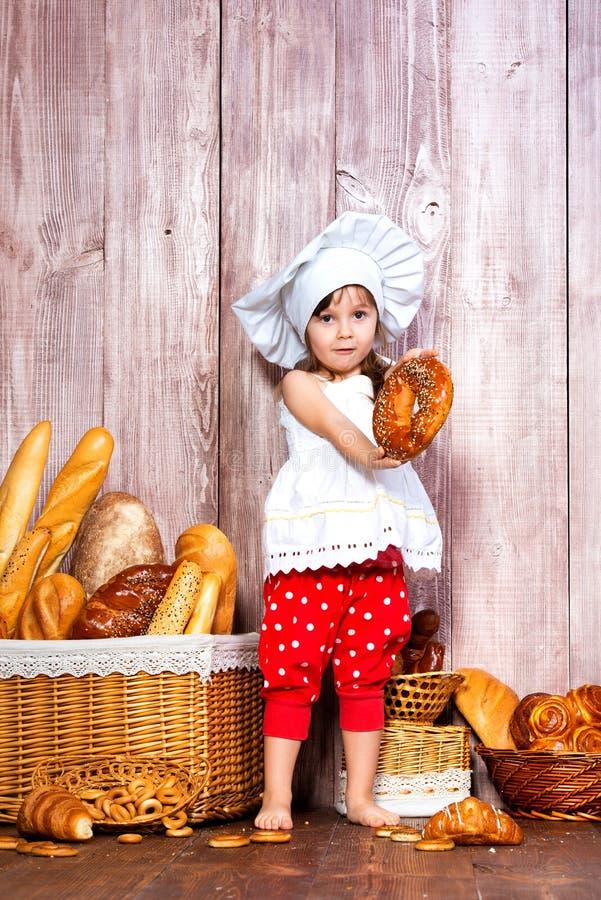 Äta nytt bröd och hemlagade bakelser Liten le flicka i ett kocklock med bageln i hand nära en vide- korg med brödrullar arkivbild