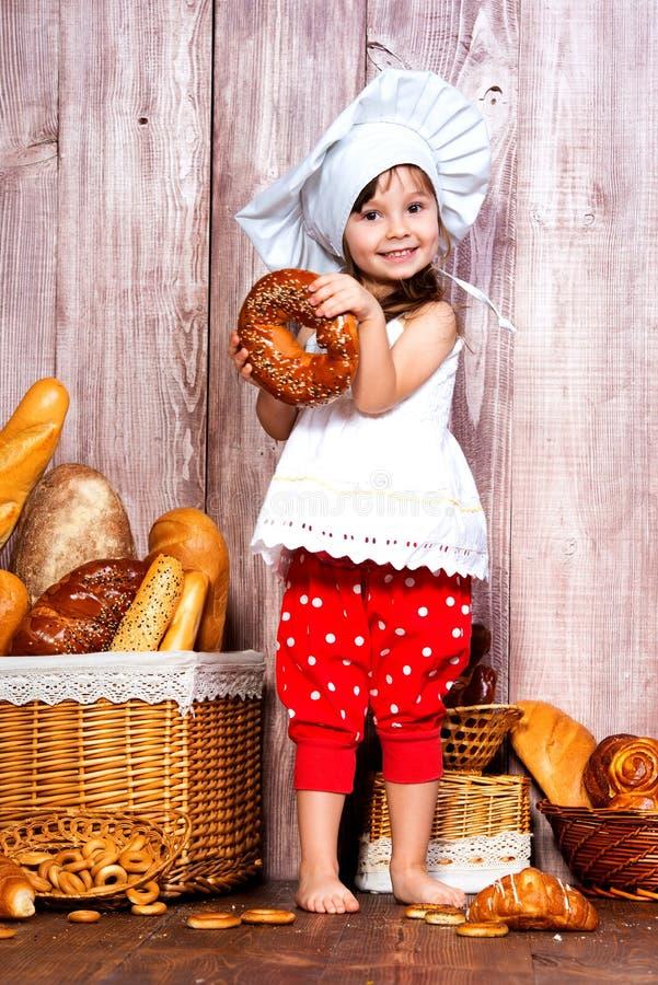 Äta nytt bröd och hemlagade bakelser Liten le flicka i ett kocklock med bageln i hand nära en vide- korg med brödrullar royaltyfri fotografi