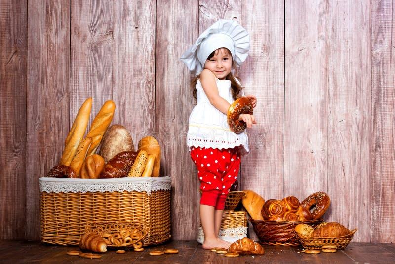 Äta nytt bröd och hemlagade bakelser Liten le flicka i ett kocklock med bageln i hand nära en vide- korg med brödrullar arkivbilder
