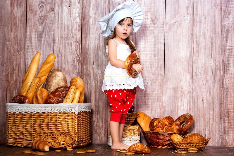 Äta nytt bröd och hemlagade bakelser Liten le flicka i ett kocklock med bageln i hand nära en vide- korg med brödrullar arkivfoto