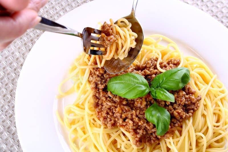Äta riktigt spagetti bolognese med gaffeln och skeden royaltyfri foto