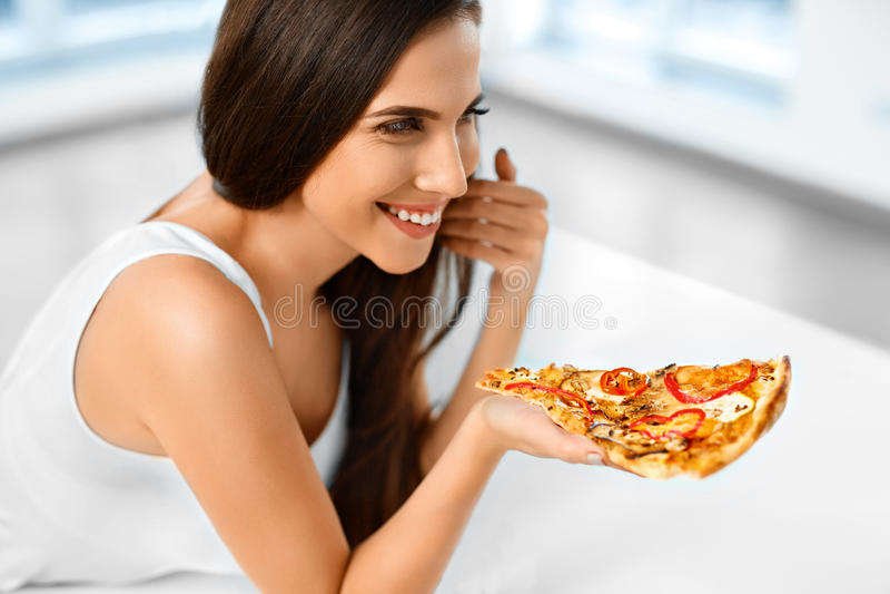 Äta snabbmat Kvinna som äter italiensk pizza näring Banta L arkivfoto