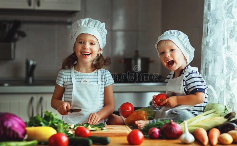äta som är sunt Lyckliga barn förbereder grönsaksallad i kitc royaltyfri foto