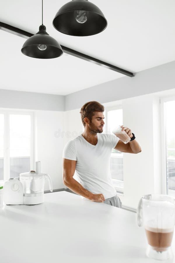 äta som är sunt Muskulös man som inomhus dricker sportskakadrinken fotografering för bildbyråer