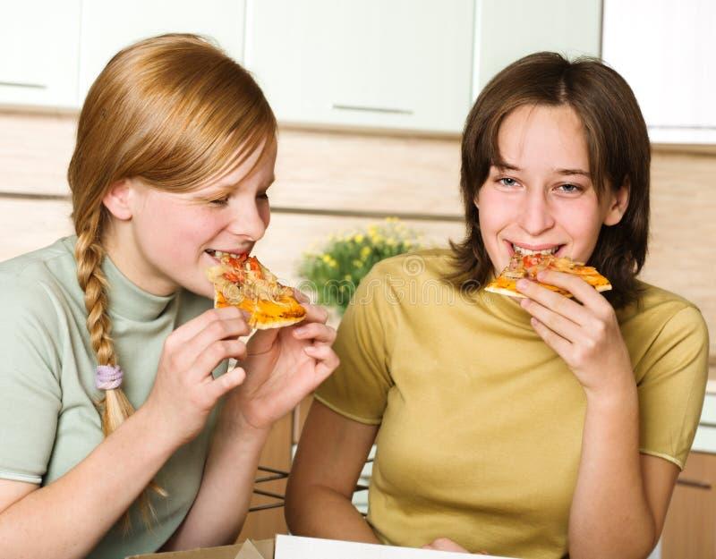 äta tonårs- flickapizza royaltyfria bilder