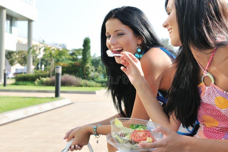 äta vänner som utmärkt utomhus har tid royaltyfri bild