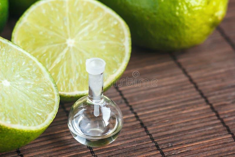 Ätherische Öle in der Glasflasche mit den frischen, saftigen, reifen Kalken Aufbau mit Badeöl und Seifen Seifen-, Tuch- und Blume stockbilder