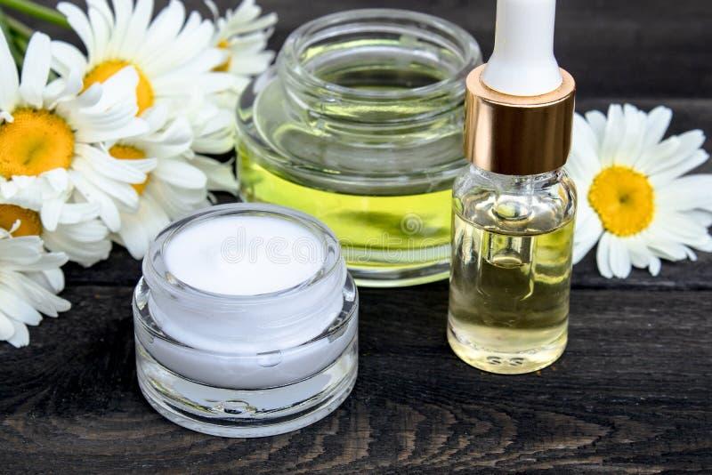 Ätherisches Öl und kosmetische Creme sind auf einem Holztisch nahe den Blumen der weißen Kamille lizenzfreies stockfoto