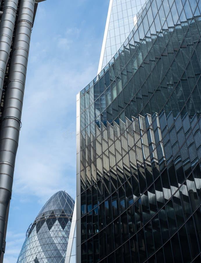 Ättiksgurkabyggnaden på 30 St Mary Axe i staden av London det finansiella området som, är synlig bak Lloyds och Willis byggnader royaltyfri bild