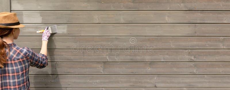 Äußere Wand des Arbeitnehmerin-Malereiholzhauses mit Malerpinsel und hölzerner schützender Farbe lizenzfreies stockbild