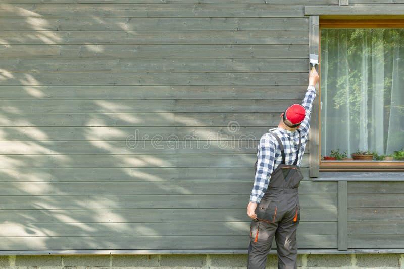 Äußere Wand des Mannarbeitskraftmalereiholzhauses mit Malerpinsel und hölzerner schützender Farbe stockbilder