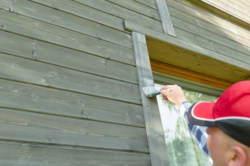 Äußere Wand des Mannarbeitskraftmalereiholzhauses mit Malerpinsel und hölzerner schützender Farbe stockbild