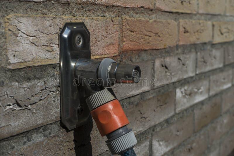 ?u?erer Metallwasserhahn, der aus normalen Hausmauerziegelsteinen heraus haftet Hauswasserhahn mit einem waterhose befestigt Makr stockfoto