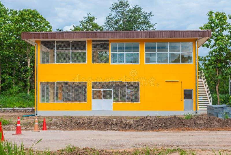 Äußeres des leeren konkreten gelben Fabrik-Lager-Gebäudes stockfotografie