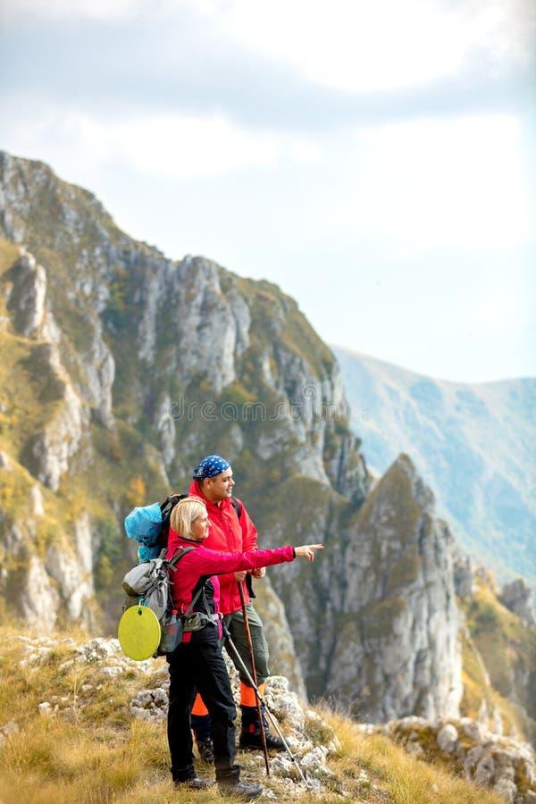 Äventyra, resa, turism, vandringen och folkbegreppet - le par som utomhus går med ryggsäckar arkivbild