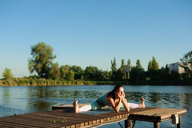 健康妇女生活方式在早晨平衡了实践思考和能量瑜伽在桥梁自然 库存照片