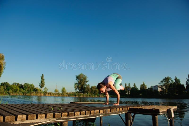 健康妇女生活方式在早晨平衡了实践思考和能量瑜伽在桥梁自然 库存图片