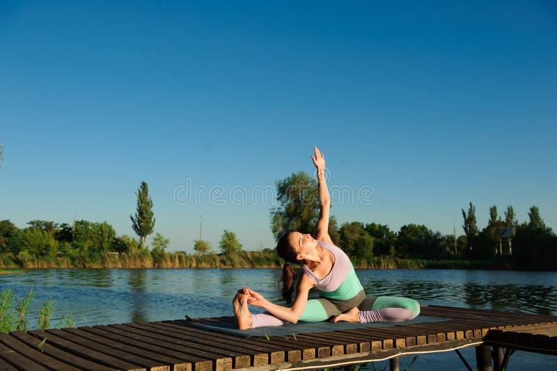 健康妇女生活方式在早晨平衡了实践思考和能量瑜伽在桥梁自然 免版税图库摄影