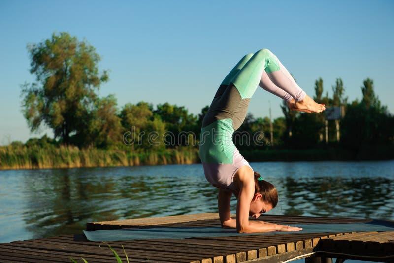 健康妇女生活方式在早晨平衡了实践思考和能量瑜伽在桥梁自然 图库摄影