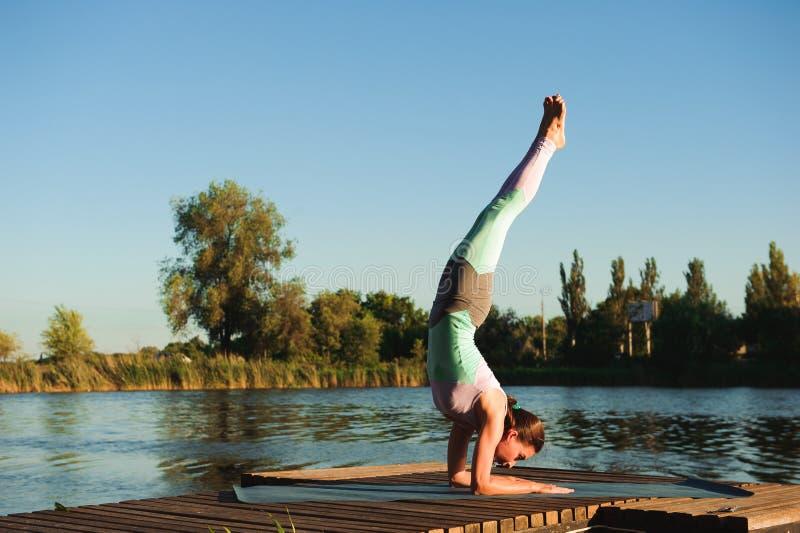 健康妇女生活方式在早晨平衡了实践思考和能量瑜伽在桥梁自然 健康 免版税库存照片