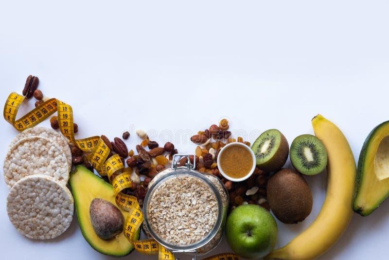 健康早餐燕麦粥用葡萄干和坚果 杏仁,蜂蜜,苹果,鲕梨,在白色桌背景的香蕉 复制空间 免版税库存照片
