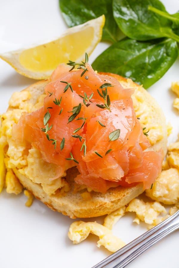 健康早餐:在一个敬酒的小圆面包的炒蛋和熏制鲑鱼三明治 免版税库存图片
