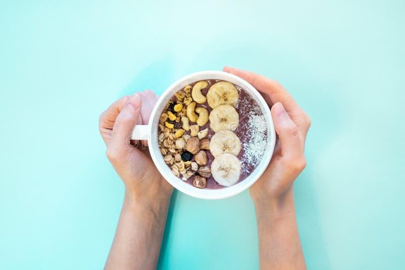 健康膳食概念:一碗与坚果和香蕉切片,顶视图的果子圆滑的人 免版税库存照片