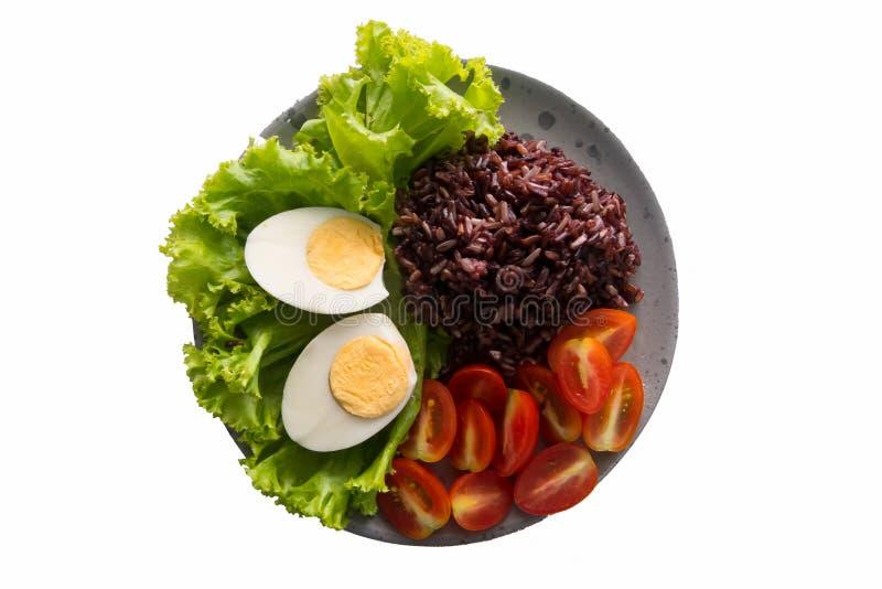 健康食品,包含糙米、米、蕃茄、熟蛋和绿色叶茂盛莴苣的干净的食物 在一张顶视图的一个盘 库存图片