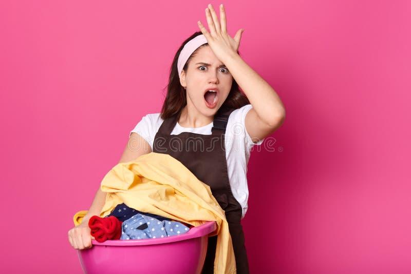 健忘女性保留在前额的手,记得她忘记买洗衣粉,穿戴在白色偶然T恤杉和围裙, 免版税图库摄影