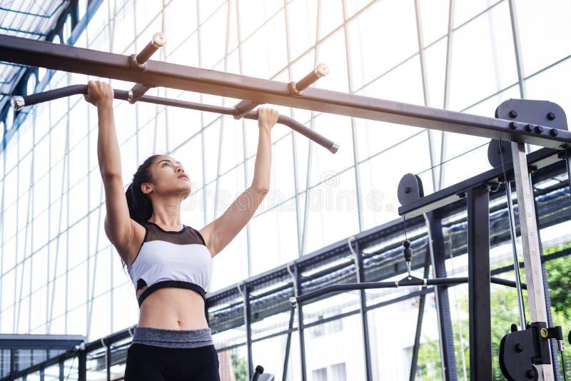 健身妇女与锻炼机器的锻炼锻炼在健身俱乐部健身房的酒吧拔 概念健康生活方式 免版税库存图片