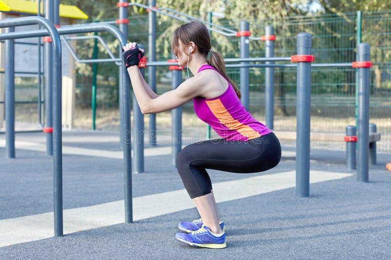 健身妇女分裂了明亮的运动服的室外美丽的亭亭玉立的女孩做分裂矮小锻炼在室外sportsgr的矮小锻炼 免版税库存图片