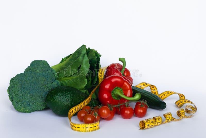 健身和健康食物的饮食概念 与菜的平衡饮食 新鲜的绿色菜,在白色背景的测量的磁带 免版税库存图片