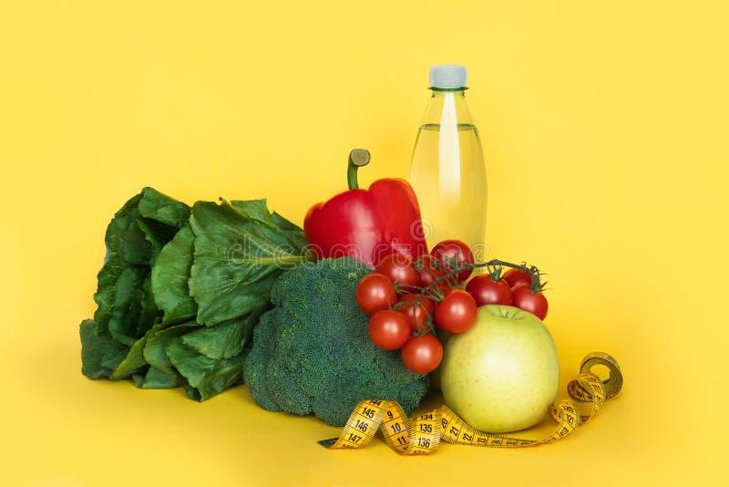 健身和健康食物的饮食概念 菜和水在黄色背景 复制空间 免版税图库摄影