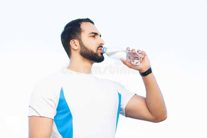 健身 年轻人休息的和饮用水在跑步以后 免版税库存照片