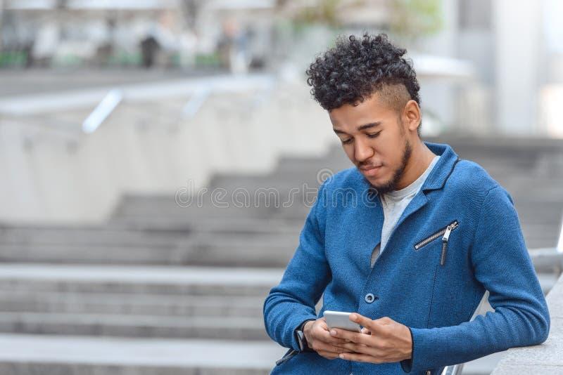 偶然聪明 混血儿倾斜在城市街道浏览智能手机特写镜头被弄脏的背景的篱芭的人身分 图库摄影
