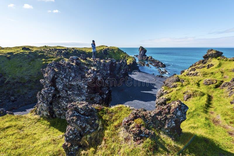 停留在熔岩岩石的上面的女孩少年观察Djupalonssandur海滩风景在冰岛Snaefellsjokull的 免版税图库摄影